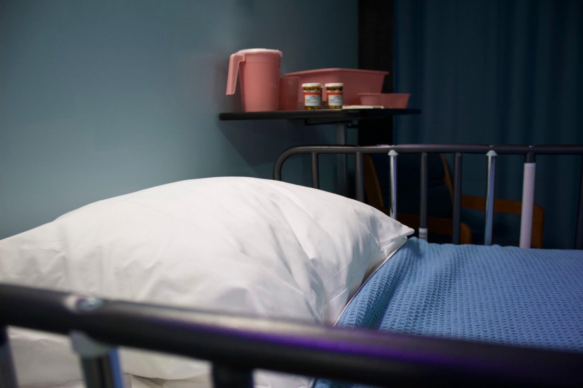 Picture of a hospital bed with bedside table next to it, on which are two boxes of pills