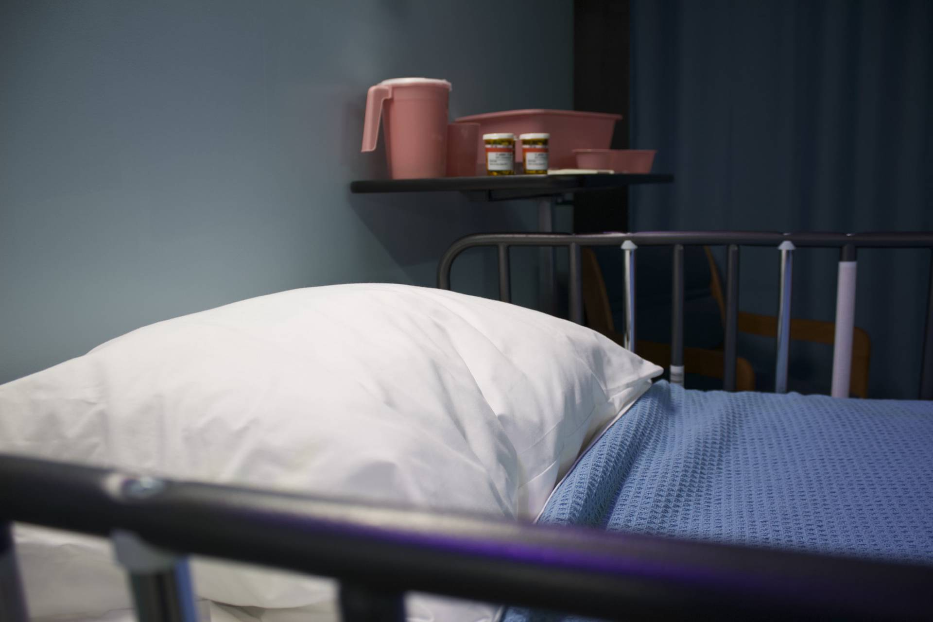 Picture of a hospital bed with a blue blanket on and white pillow, and a shelf that has a jug of water and two boxes of pills. The room is dark and there is a green curtain in the background