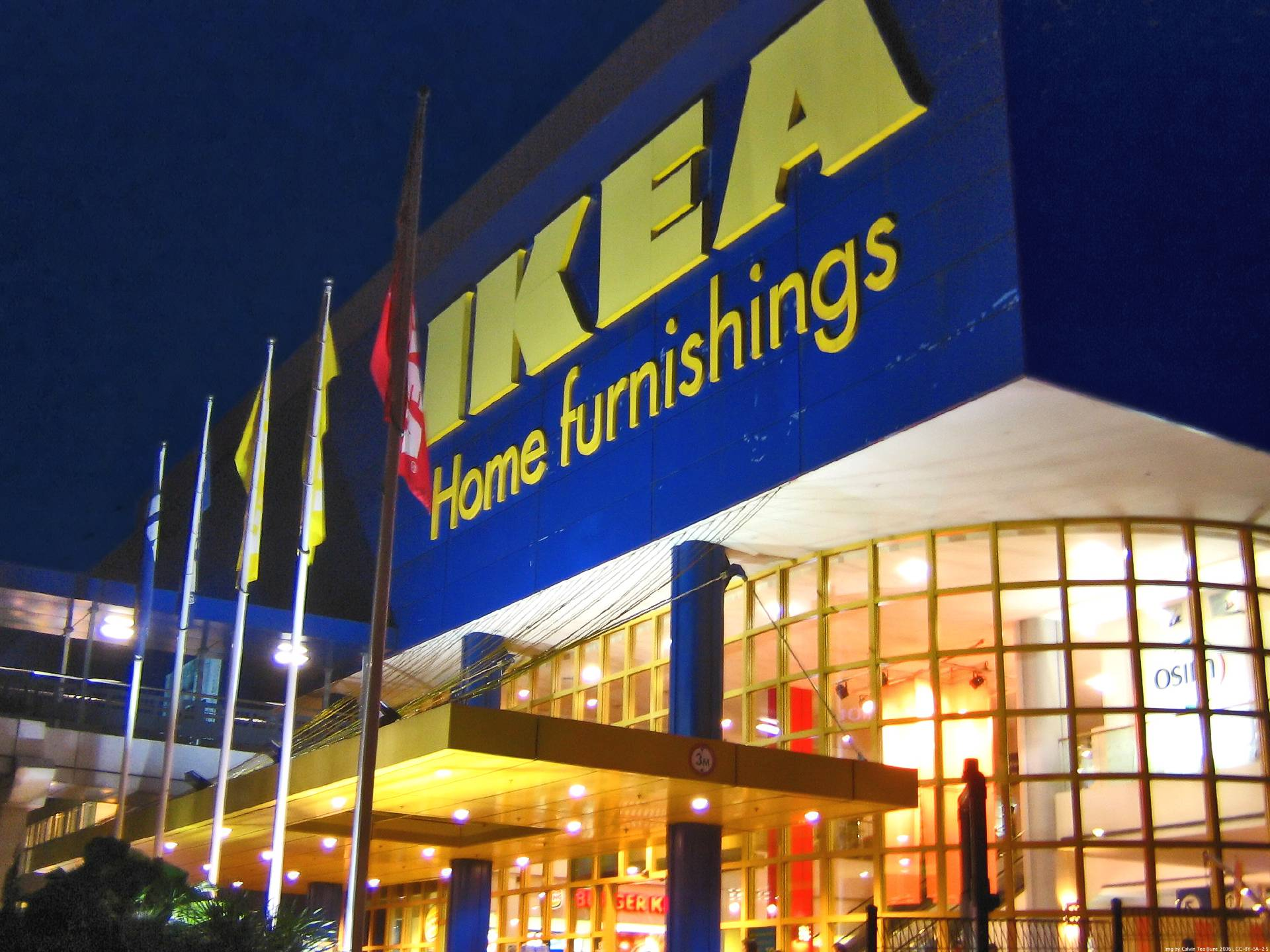 Picture of the store entrance for IKEA, with a series of flags. The building lights are switched on.